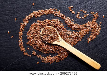 Organic Flax seeds in wooden spoon on black slate stone plate