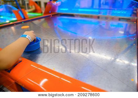 little kid plays in air hokey in Entertainment Center