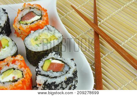 Sushi roll mix on plate with wooden chopsticks