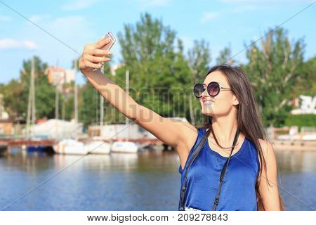 Beautiful young tourist taking selfie on river bank
