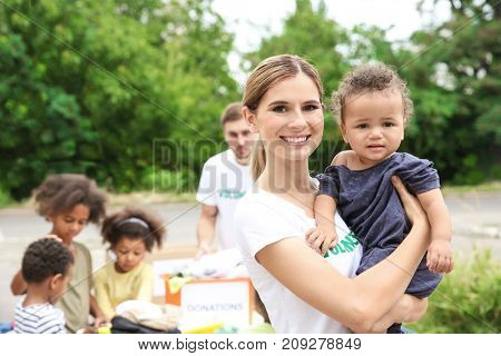 Young female volunteer holding little African girl outdoors