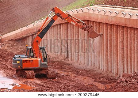 Digger scraping concrete support pillars on a construction site