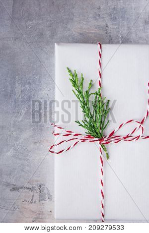 Elegant Gift Box Wrapped in White Paper Tied with Red Ribbon Green Juniper Twig. Christmas New Years Presents Shopping Sale. Metallic Grey Background Copy Space