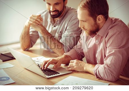 Entering information. Serious smart handsome man sitting in front of the laptop screen with his colleague and pressing buttons on the keyboard while entering information