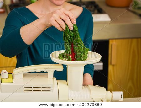 Woman using a centrifuge machine to prepare a detox juice.