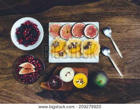 Healthy breakfast set on rustic wooden table. Superfoods smoothies bowl with chia seeds and acai pulver, pomegranate, blackberries, dessert. Overhead, top view, flat lay style.