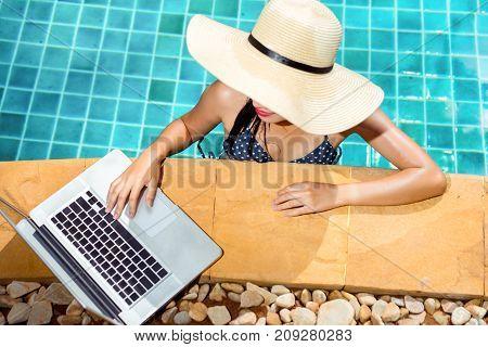 Woman bikini using laptop computer blank screen at swimming pool in resort edge