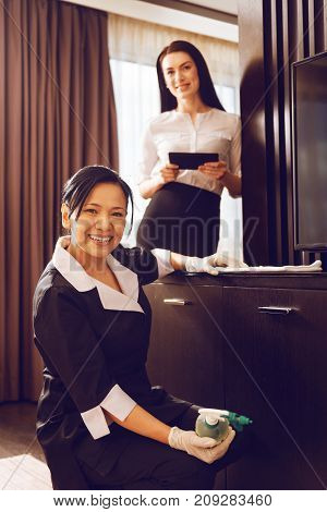 Love my job. Delighted brunette working at hotel, leaning arm on chest of drawers while keeping smile on her face