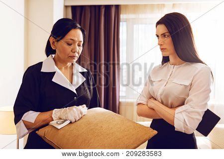 Angry with you. Upset hotel staff being in uniform and bowing head while looking at dust on pillow