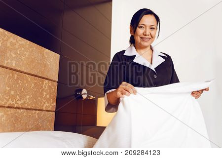 Preparing bed. Beautiful hotel staff keeping smile on face and holding blanket while looking straight at camera