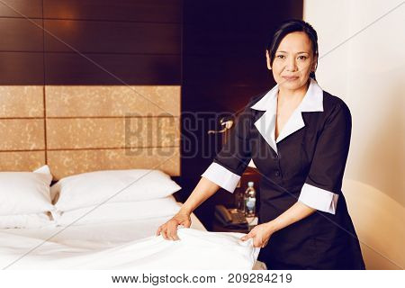 Hard work. Attractive international worker standing in semi position and looking at camera while making bed