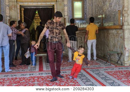 Fars Province Shiraz Iran - 19 april 2017: Shah Cheragh Shrine Father and son leave the mosque after prayer.