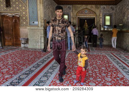 Fars Province Shiraz Iran - 19 april 2017: Shah Cheragh Shrine A man leaves the mosque after a prayer and holds the hand of a small child.