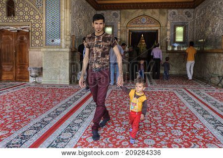 Fars Province Shiraz Iran - 19 april 2017: Shah Cheragh Shrine man comes out of the mosque with a little boy whom he leads by the hand.