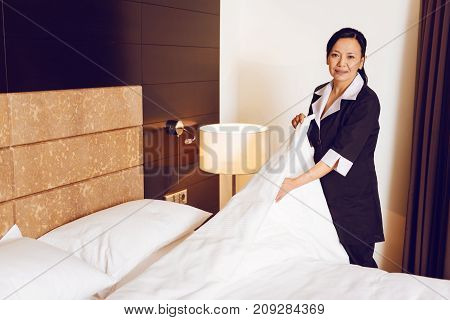 Making bed. Delighted brunette keeping smile on her face and standing on the background while holding blanket