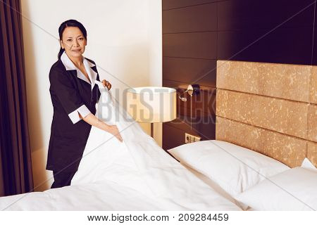 Put in order. Attractive hotel worker expressing positivity and holding quilt while covering bed in VIP room