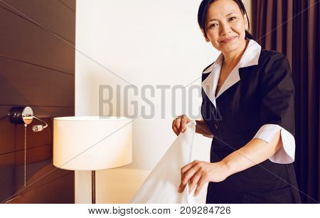 Smile and do. Beautiful woman wearing uniform and expressing positivity while working in hotel