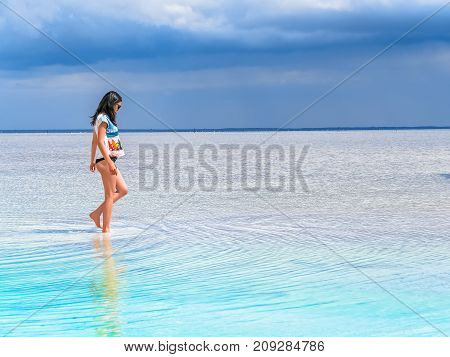 A girl walks along the surface of a salt lake at a spa resort. Young woman on the beach with white sand and beautiful scenery around.