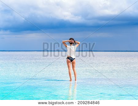A girl stand on the surface of a salt lake at a spa resort. Young woman on the beach with white sand admires beautiful scenery around.