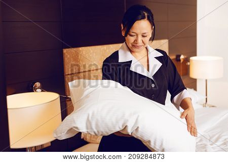 Putting it straight. Delighted maid keeping smile on her face and wearing uniform, checking bedclothes