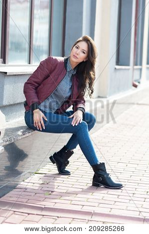 Young Beautiful Stylish Woman In A Burgundy Pilot's Jacket And Blue Jeans, Street Style, Spring And