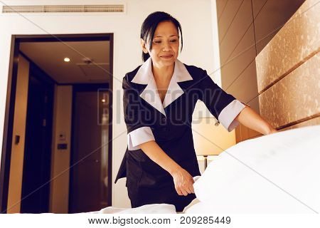 Nice smile. Positive female keeping smile on her face and looking downwards while making bed