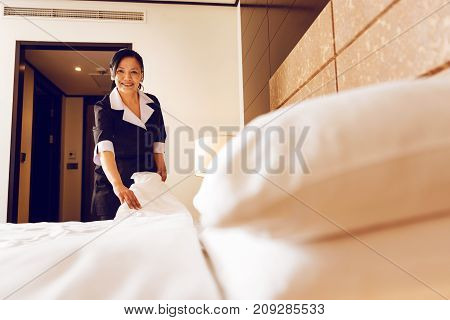 Working day. Cheerful international room cleaner holding quilt in both hands and standing behind big bed while looking straight at camera