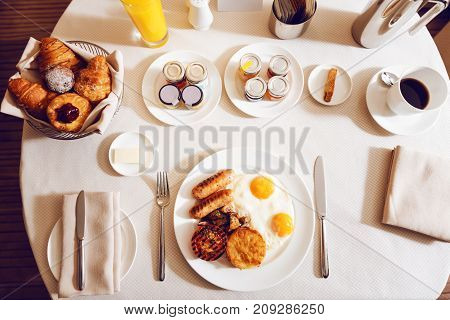 Table appointments. Big plate being full of fried eggs and sausages, standing on round table