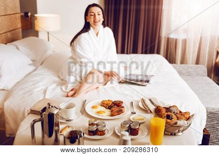 Enjoy your meal. Positive delighted brunette keeping smile on her face and examining magazine while sitting on bed