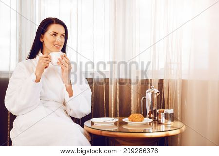 Positive thoughts. Attractive woman keeping smile on face and holding white cup while looking aside