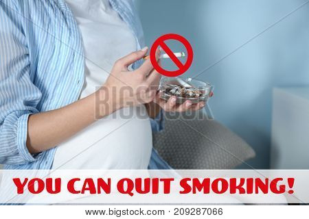 Pregnant woman with cigarette sitting at home. Text YOU CAN QUIT SMOKING