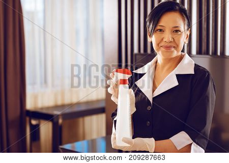 Good cleaner. Professional hotel maid holding bottle in both hands while posing on camera and expressing positivity