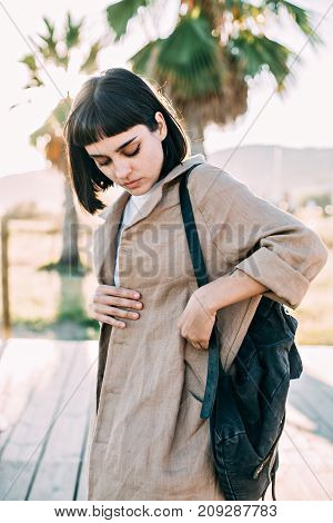 Attractive pretty woman in linen or cotton designer coat and leather backpack stands in warm evening light looks inside her pocket searching for smartphone or make up