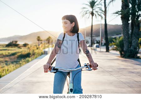 Attractive hipster millennial woman or teenager in blue american denim and simple white tshirt rides bicycle on sunset promenade next to beach authentic tattoos