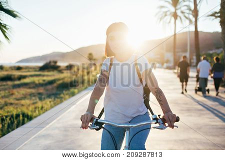 Attractive adorable woman rides her beach cruiser bike on promenade boardwalk sunshine light beams in her hair arm tattoos as cool hipster end of summer mood weather