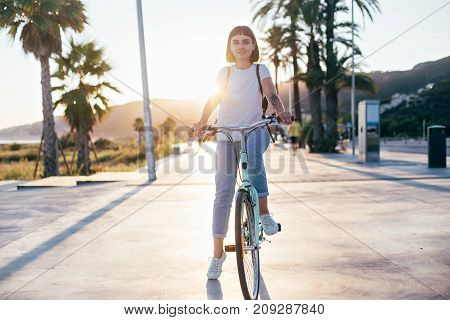 Happy beautiful hipster millennial woman or teenager with cool arm tattoos is tourist in summer of spain or italy she rides rental cruiser bicycle happy and relaxed enjoying youth and freedom