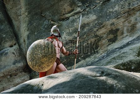 Strong muscular medieval warrior with sexy body and perfect abs wearing a helmet holding a spear and a shield looking away thoughtfully.