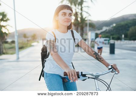 Attractive and stylish trendy fashionable student in white tshirt and leather backpack she smiles gently and smirks into camera soft sunlight while she rides commuter bicycle