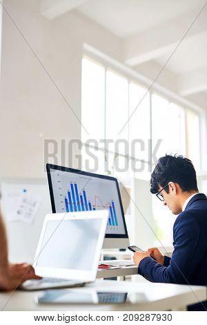 Busy manager texting in smartphone while sitting in front of computer monitor with financial chart and graph