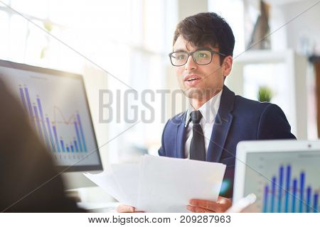 Accountant with papers consulting with co-worker about financial development