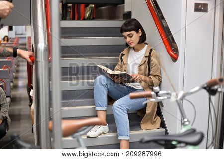 Attractive brunette woman or teenager sits on stairs of double decker train, female student studies or prepares for exams on early morning commute