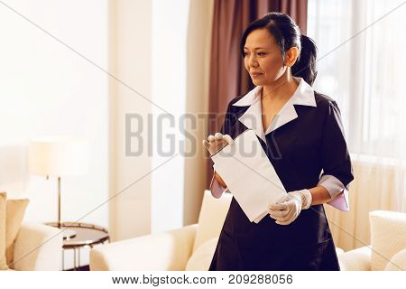 Put it here. Cheerful brunette standing in semi position and holding duster while looking aside