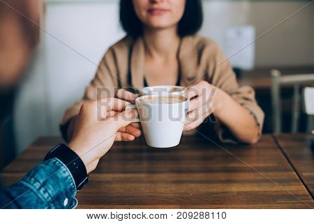 Man proposes gives coffee in white little cup to his girlfriend or partner they are in love and are on romantic date in downtown stylish cafe or restaurant drink artisan speciality