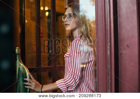 Portrait of beautiful young blonde woman in hipster prescription glasses made through glass window with light leaks on her face to add vintage retro touch smiles when opening door
