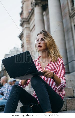 Attractive smiling woman with blonde hair wears business official red shirt sits on steps of office building outdoors during lunch break works on project or studies on laptop