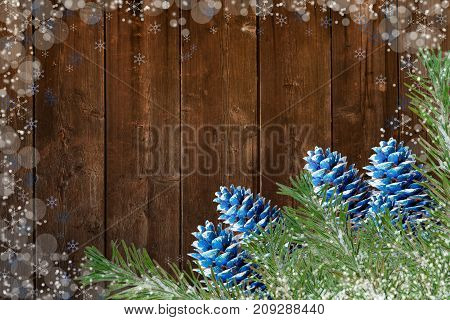 Fir Branches And Blue-colored Cones On Old Wooden Boards Backgrounds With Painted Snowflakes And Sno