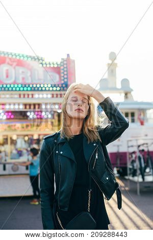 Portrait of beautiful attractive young model posing for camera in sunset light wears black hipster leather jacket and cool trendy glasses. Fashion conscious millennial at carnival fair