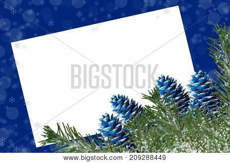 Snow-covered Fir Branches And Blue-colored Cones On Blue Backgrounds With Snowflakes And Copy Space
