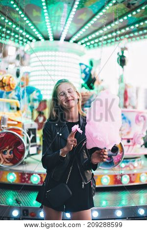 Adorable cute pretty woman stands in middle of amusement park in front of ride with bright colours positive and cheerful eats pink cotton candy floss happy and optimistic