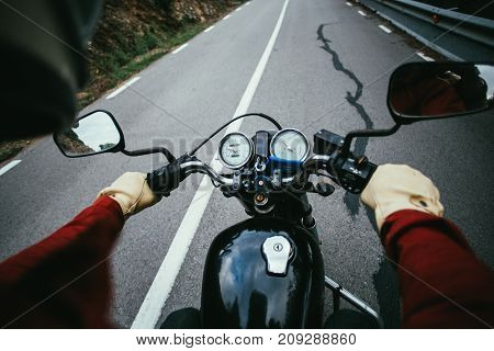 Overhead shot of male biker in red jacket and protective gloves driving and maneuvering big chopper or cafe racer motorcycle on mountain road hands on steering wheel